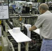 Eddie Goldsmith feeds a folder-gluer at the PaperWorks Industries plant in Greensboro. The company will add additional folder-gluers as it expands capacity with its relocation to Rock Creek Center.