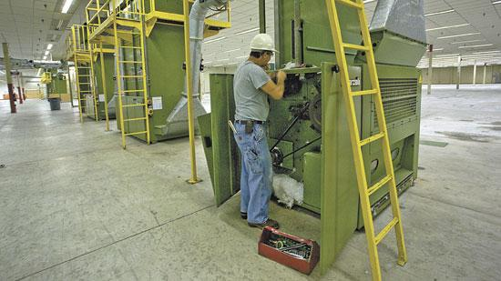 Danny Williams, technician for Glen Raven Inc., works on equipment in a plant the company is converting for highly automated yarn production.