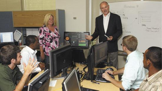 Mark Wright, standing, chief information officer for Inmar Technology Solutions in Winston-Salem, leads a class for IT interns, with the assistance of web developer Lisa DeWitt. Inmar is taking advantage of the booming growth of online coupons.