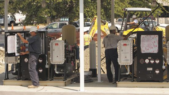 Natural gas technicians with Piedmont Natural Gas work on the new refueling station being built at the PNG Resource Center in Greensboro.
