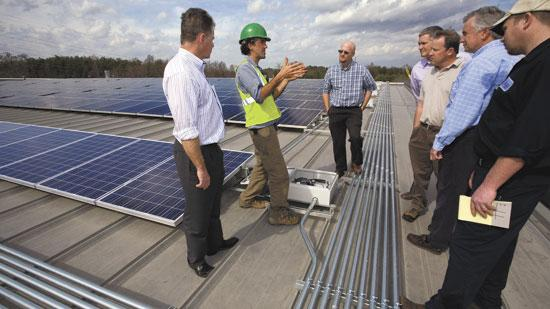 Bruce Freeman, left, president of Skyward Solar Power, and David Del Vecchio, in hardhat, senior engineer with Strata Solar, talk with a group with Tencarva Machinery about the solar panels recently installed on their roof.
