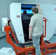 Jay Geer, an aviation student at GTCC, stands outside the school's flight simulator.