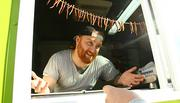 Nick Benshoff, the 25-year-old proprietor of the Bandito Burrito food truck, serves a customer.