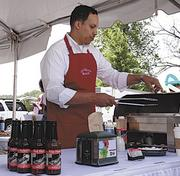 John Parker, hands out samples of meat cooked in his Guy Parker's Old Fashioned Bar-B-Q Sauce at a Fresh Market festival recently in Greensboro.