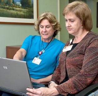 Health care navigators from Forsyth Medical Center and Wake Forest Baptist Health confer on shared medical records software in an effort to cut preventable readmissions.