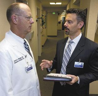 Steve Neorr, right, vice president and executive director of Triad HealthCare Network, talks with Dr. Patrick Wright, division chief at LeBauer Pulmonary & Critical Care Medicine.