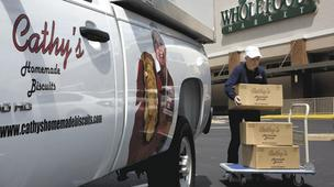 Cathy Dunn, owner of Cathy's Homemade Biscuits, unloads boxes of biscuits at Whole Foods Market in Greensboro. Dunn is also responsible for placing her product in the frozen foods section of the store.