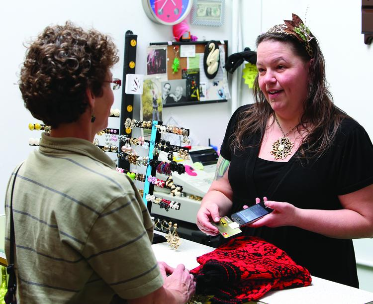 Susan Watson, owner of Wild N Crazy Vintage in downtown Greensboro, uses Square to process credit card purchases in her store.