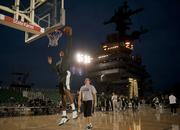 Michigan State University basketball player Adreian Payne dunks during a practice in the basketball arena on the flight deck aboard Nimitz-class aircraft carrier USS Carl Vinson.