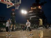 Michigan State University basketball player Alex Gauna dunks during a practice in the basketball arena on the flight deck aboard Nimitz-class aircraft carrier USS Carl Vinson.