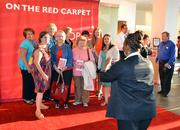 An usher at the DPAC takes a photo of ladies on the red carpet.