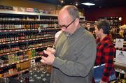 Scot Covington signs a bottle of one of his award-winning wines at Bottle Mixx.