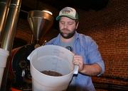 Videri Chocolate Factory's Sam Ratto holds up a container of freshly roasted cocoa beans.