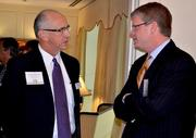 Sig Hutchinson, left, with Sig Hutchinson Communications networks with Time Warner Cable's Keith Poston.