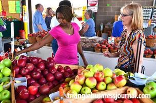 Lydia Aryee, left, helps Jan Peacock find the perfect apple at the North Carolina State Farmers Market in Raleigh.