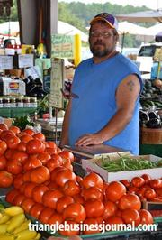 Jeff Allen displays a colorful assortment of locally grown tomatoes at the North Carolina State Farmers Market.