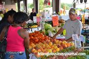 Shoppers look over the fruits and vegetables at the farmers market in Raleigh.