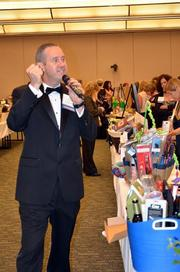 Live auctioneer Benjamin Farrell makes his way through the silent auction room trying to boost sales of some of the items.