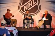 Former Carolina Hurricanes players and current team executives Glen Wesley, left, and Rod Brind'Amour chat with team Hall of Fame radio voice, Chuck Kaiton.