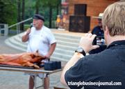 A spectator at the  festival takes a photo of a live pig picking.