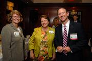Finalist Mona Moon, left, talks with fellow N.C. State Health Plan employee Lucy Barnes and Keith Erazmus of sponsor BofA Merrill Lynch.