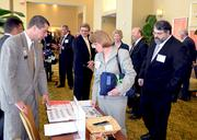 Finalist Mona Moon with the State Health Plan checks the TBJ display. Looking on is Mike Moon.