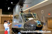A man shows his kids the inside of a Vietnam era UH-1 Helicopter.