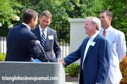 Doug Vinsel and John Kane shake hands as part of the new Midtown Raleigh Alliance.