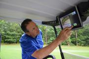 Ed Ibarguen, general manager and director of golf operations at Duke University Golf Club, demonstrates the features on the interactive scorecard.