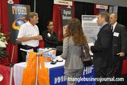 Employees with Mindshift Technologies Inc. talk to several attendees at the growth expo.