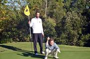 Mike Perry of Governors Club helps TBJ's Cameron Snipes line up a putt.