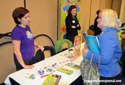 An employee with Marbles Kids Museum talks with an attendee at the health expo.