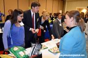 While showing off some of Carolina Vending's healthy options, Shannon Craige talks with a handful of interested attendees.