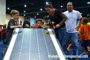 A kid takes his race car creation down the slope at the race ramp area of the Lego Kidsfest.