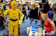A girl poses next to R2-D2 along with his trusty counterpart, C3P0.