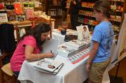 A young fan gets a book signed by Chef Maneet.