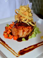 One of Chef McCall's signature dishes is a grilled 8 oz. pork chop with crispy caramelized  onions, vegetable ratatouille and pesto risotto with a pork deem sauce. This item sells for $32 on the dinner menu.