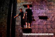 A couple of the Dralion trampoline performers relax on the stage's backdrop. This metallic backdrop is 60 feet wide and 26 feet tall.