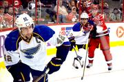 St. Louis Blues captain David Backes in the foreground, with Blues player Andy McDonald and Carolina Hurricanes Jussi Jokinen in the background.