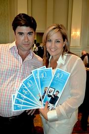 Winners Arik Abel and Alisha Whiteway pose with a collection of award programs.