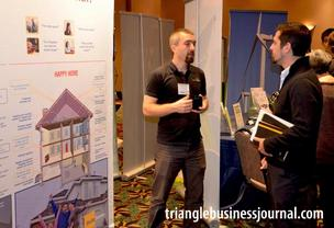 Bradley Yoder with Build Sense|Studio B Architecture discusses his business model with an attendee at the Green Expo.