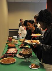 Employees with Parata Systems enjoy a table full of festive desserts at their company party.