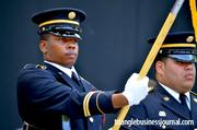 A solider holds the flag at attention during the singing of The National Anthem.