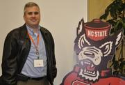 EMC (NYSE: EMC) system engineer Chris Roscoe poses with the N.C. State mascot.