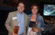 John Bell and Mary Rich Hill pose with a couple of bottles of Troy & Sons whiskey.