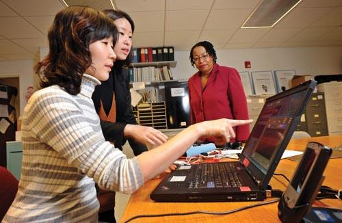 As Associate Professor Debra Barksdale looks on, students Jeongok Logan, foreground, and Minhee Suh evaluate data in a lab at UNC's School of Nursing.
