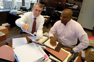 From left, law firm partner Drew Campbell discusses a case with young litigator Anthony Sharett.