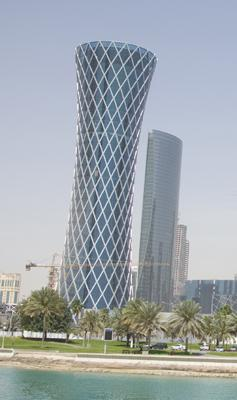 The hourglass-shaped building with the green glass and the white diamond-shaped latticework is the Tornado Tower in Doha, Qatar, where two K&L Gates attorneys work.