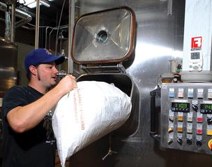 Head brewer Chris Davis pours malt into a vat at Fullsteam Brewery in Durham.
