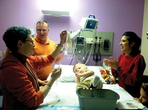 Dr. Joanne Kurtzberg holds umbilical cord blood cells for baby Jase. Parents John and LeaAnn Howell look on.